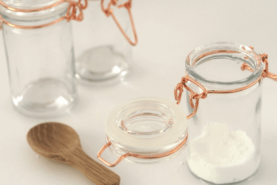 glass jars with baking soda and wooden spoon