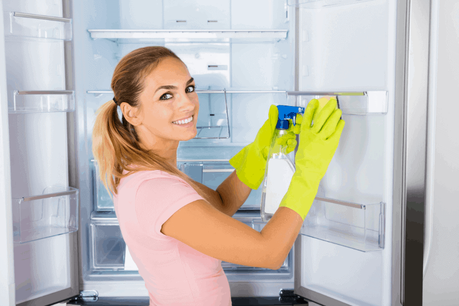 woman cleaning refrigerator with green gloves